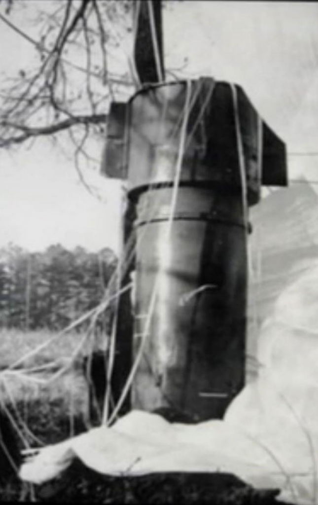 U.S. Airforce image shows undetonated nuclear bomb with deployed parachute entangled in some tree branches adjacent to a cotton field in rural eastern North Carolina.